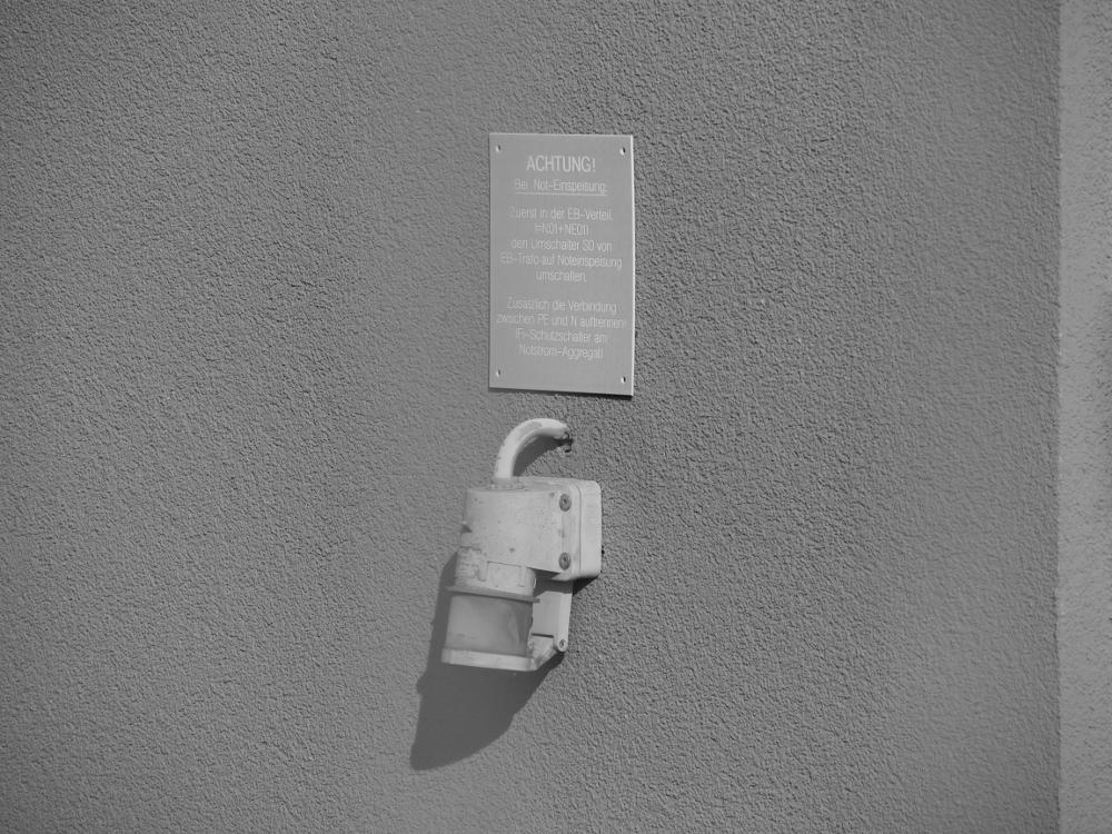 Das s/w-Foto zeigt einen Einspeise-Stecker an der Trafostation für die Noteinspeisung mit einem Schild, wie bei einer Noteinspeisung zu verfahren ist.