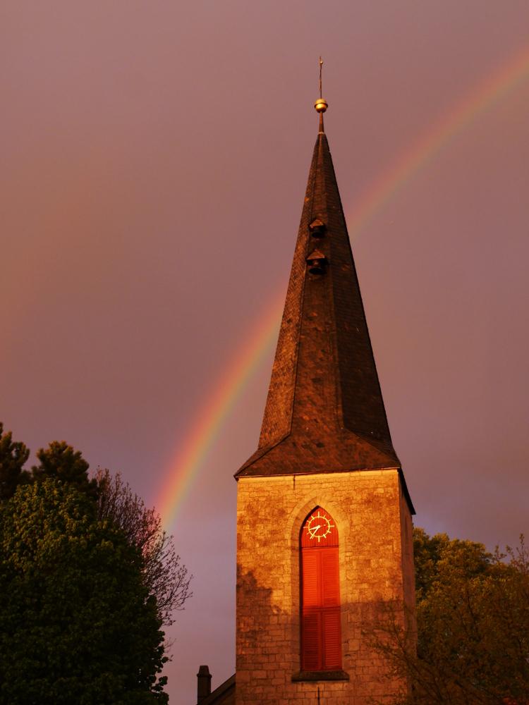 Dasa Foto zeigt den Kirchturm der Apostelkirche in Winnigstedt in der Abendsonne, hinter dem Kirchturm geht ein Regenbogen durch den wolkigen Himmel