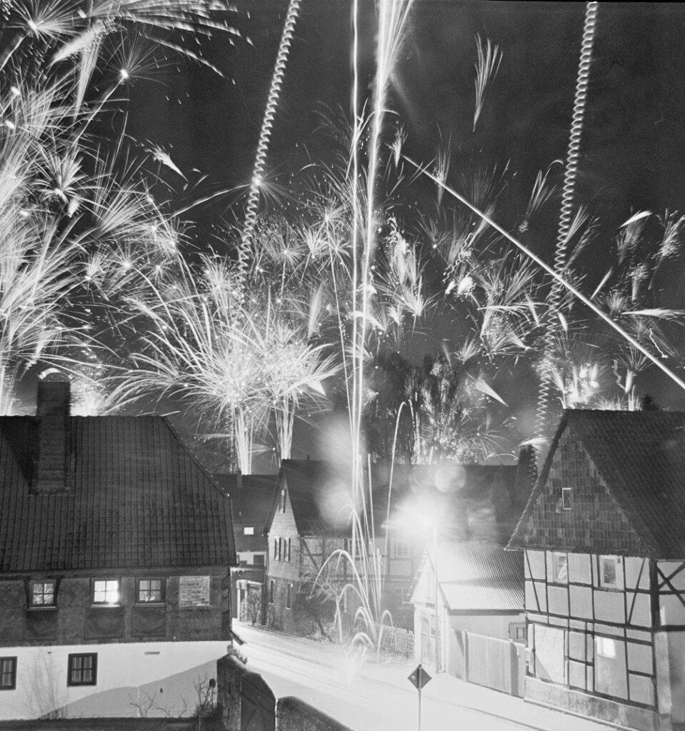 Das s/w-Foto zeigit das Silvesterfeuerwerk auf einem Dorf. Durch eine sehr lange Belichtung kann men eine Vielzahl von Leuchtspuren der verschiedenen Feuerwerkskörper sehen.