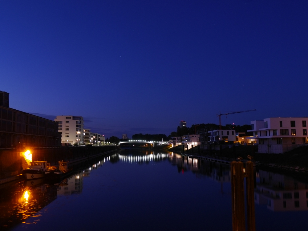 """Das Foto zeigt eine Nachtaufnahme vom Luitpoldhafen, man sieht die Schneckennudelbrücke die über den Reinarm geht, links und rechts vom Hafenbecken die Neubauten, aber auch ein wenig vom """"richtigen"""" Hafen."""