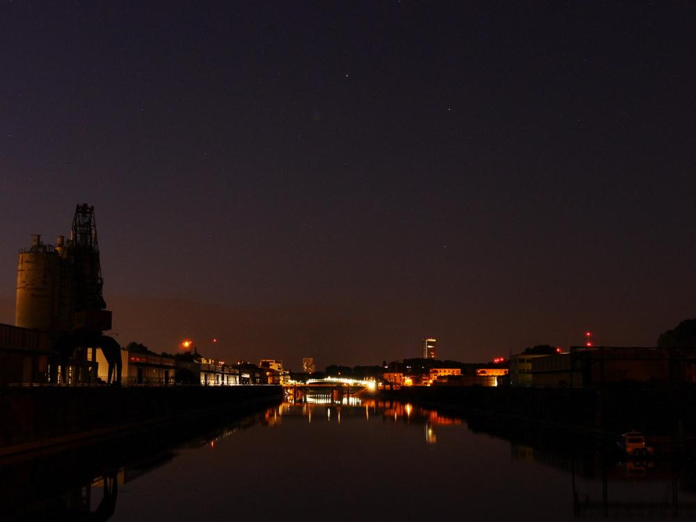 Eine Nachtaufnahme vom Luitpoldhafen, mann sieht im Hintergrund Hochhäuser und die Schneckenudelbrücke, links ist ein großer Hafenkran.