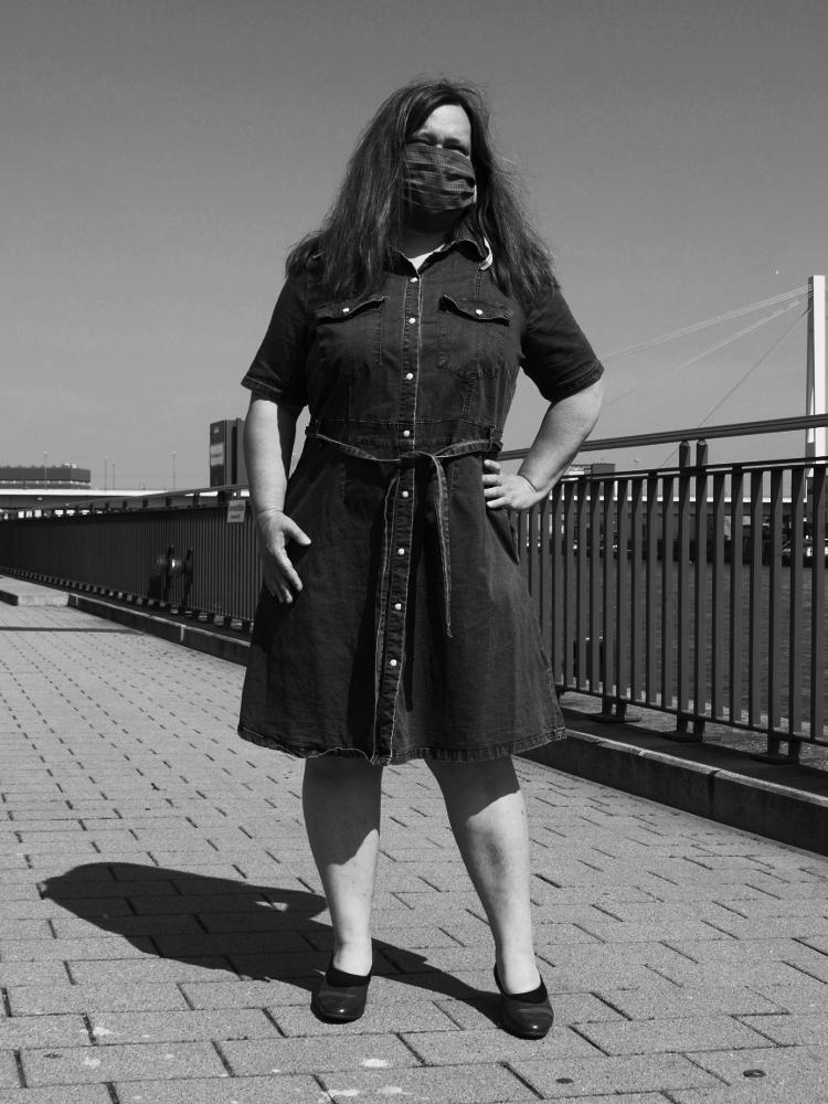 Das s/w-Foto zeigt eine Frau, die in einem Jeanskleid am Rhein steht und im Gesicht eine Stoffmaske trägt