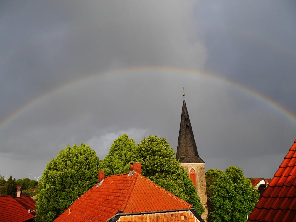 Die Landschaftsaufnahme zeigt einen Regenbogen über den Dächern und über dem Kirchturm etwa in Bildmitte.