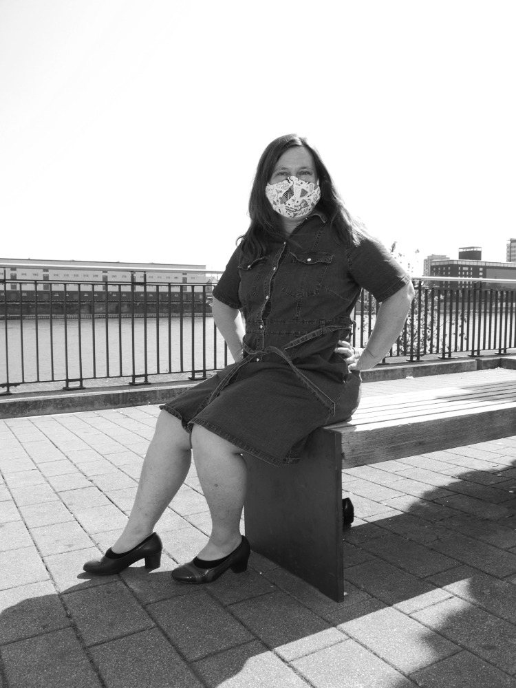 Das s/w-Foto zeigt eine Frau im Jeanskleid, die am Rheinufer auf einer Bank sitzt und im Gesicht eine Stoffmaske trägt.