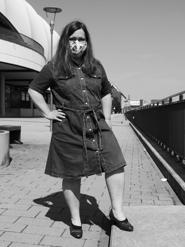 Das s/w-Foto zeigt eine Frau am Rheinufer an einem Einkaufszentrum im Jenaskleid und mit Maske im Gesicht