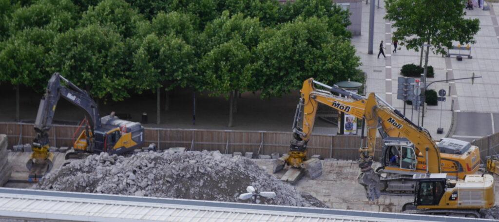 Das Foto zeigt drei gelbe Baustellen-Bagger, die um einen Schuttberg herumstehen.