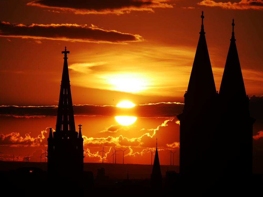 Das foto zeigt die untergehende Sonne, die zwischen Kirchtürmen steht und die von einem Wolkenband durchtrennt wird.