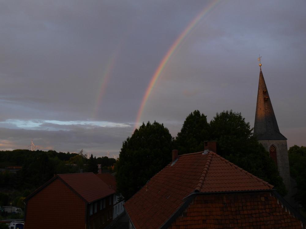 Das Foto zeigt zei Regenbögen links neben einer Kirche über dem Dorf.
