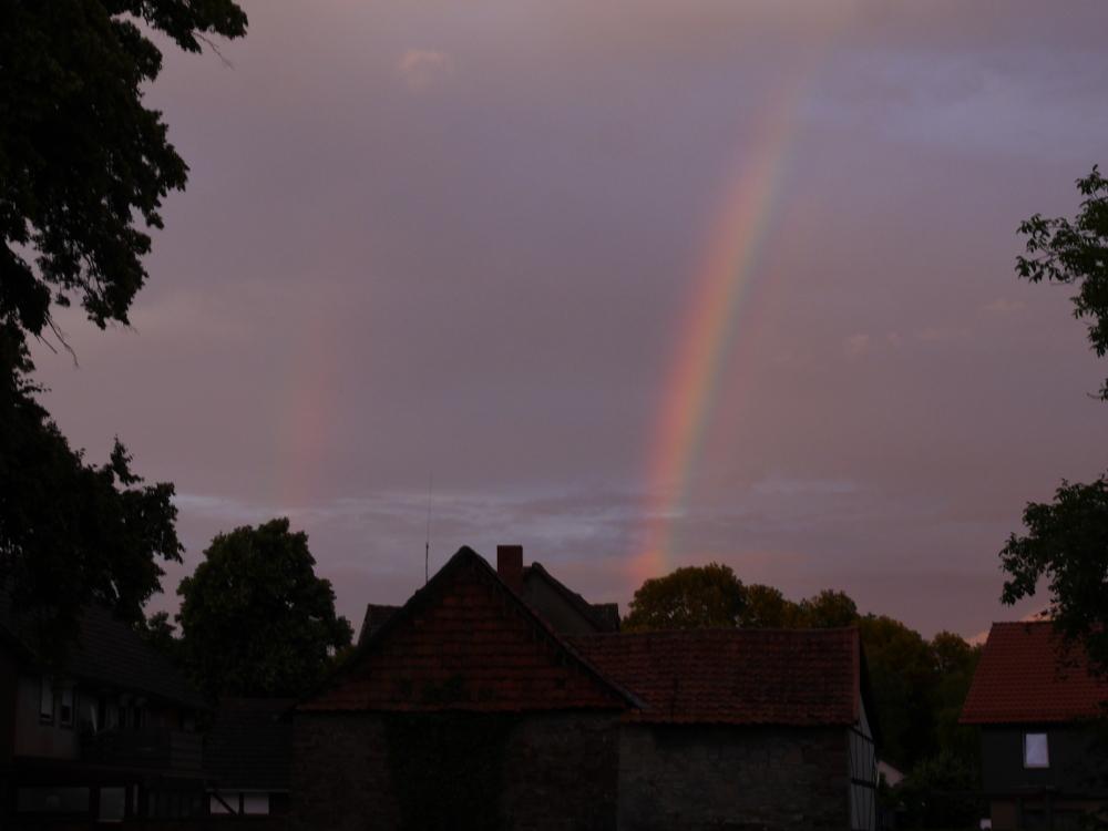 Das Bild zeigt zwei Regenbögen über dem Dorf, der rechte ist gut sichtbar, der linke leider schwach und mehr zu erahnen als zu sehen.