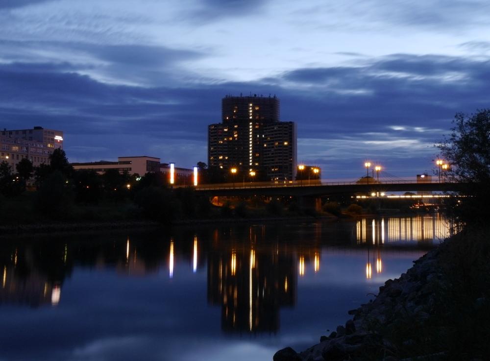 Das Foto zeigt ein Hochaus mit drei Türmen an einem Fluss. Vor den Türmen geht eine Straßenbrücke über den Fluß. Es ist dunkel, man sieht wie sich die LIchter im Fluss spiegeln.