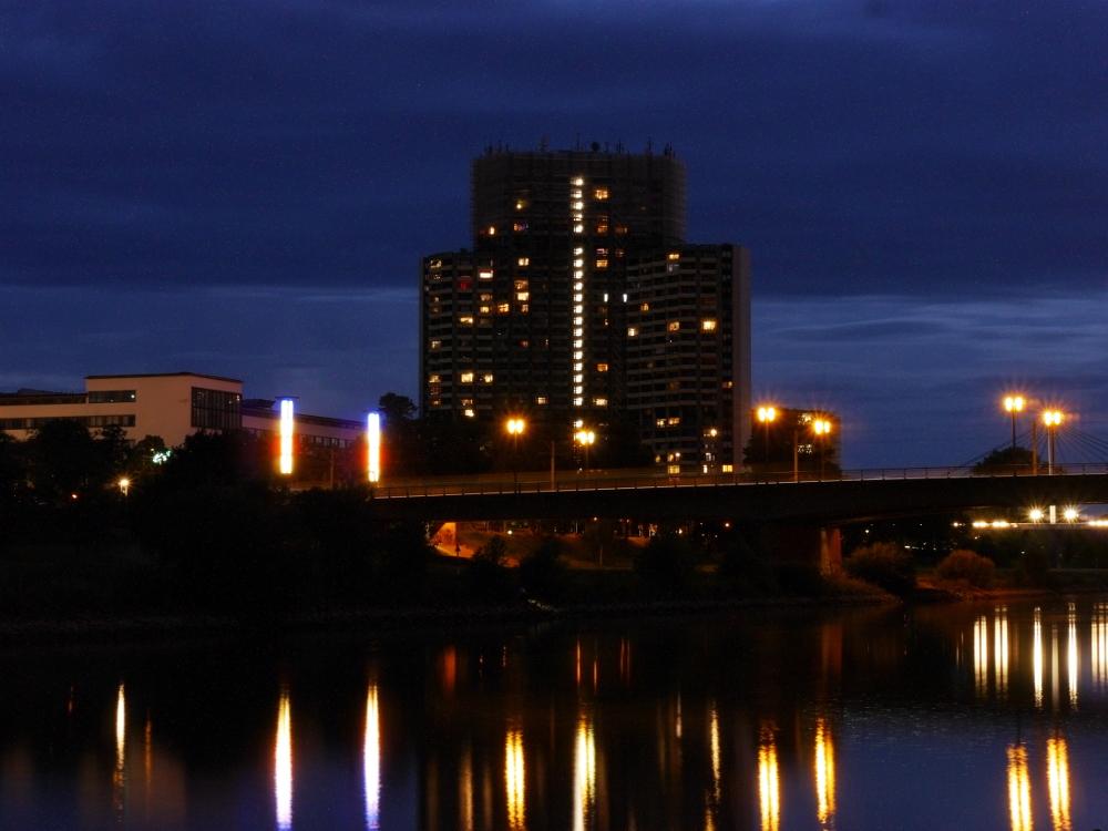 Das Foto zegit ein Hochaus mit drei Türmen an einem Fluss. Vor den Türmen geht eine Straßenbrücke über den Fluß. Es ist dunkel, man sieht wie sich die LIchter im Fluss spiegeln.