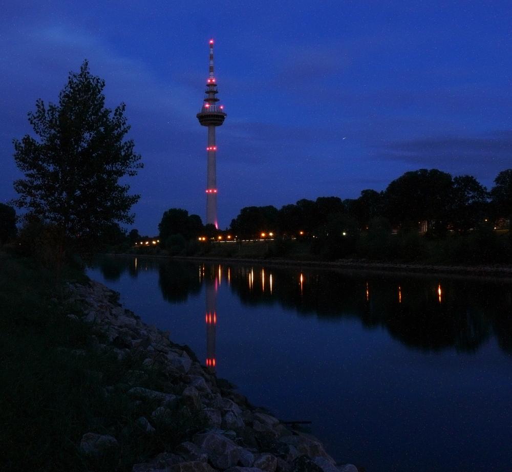 Das Fpto zeigt den Wasserturm von Mannheim bei Dunkelheit. Der Turm spiegelt sich im Neckar.