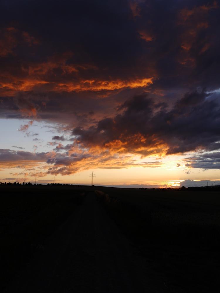 Dasa Bild zeigt einen Himmel mit dichten und teils durch die Sonne angeleuchteten und fast glühenden Rolken, ausserdem kann man einen Feldweg erahnen und es gibt Freileitungsmasten, die irgendwo im Horizont verschwinden.