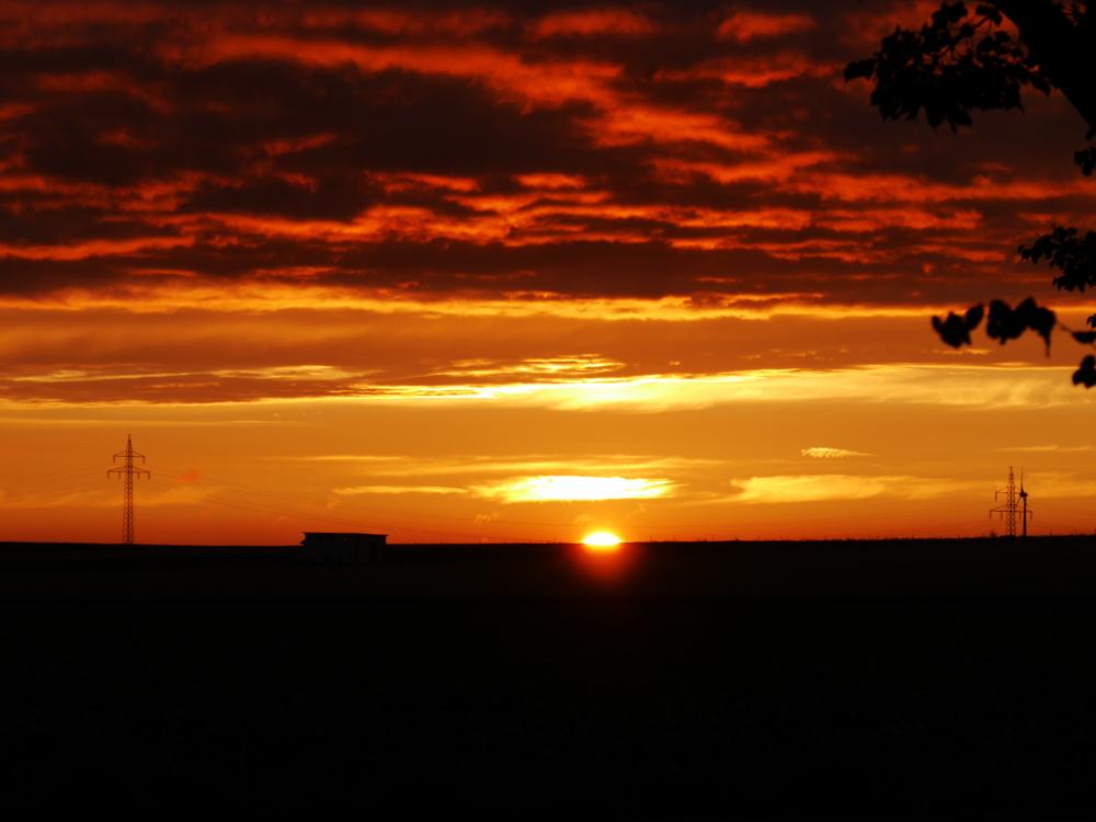 """Das Foto zeigt einen Sonnenuntergang bei wolkigem Himmel, die Sonne ist schon ca. 2/3 untergegangen und alles wirkt """"dramatisch"""", als wenn der Himmel brennen würde."""