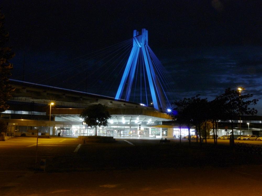 Das Bild zeigt den Hauptbahnhof von Ludwigshafen. Gut sieht man die Brücke, die sich über den Hauptbahnhof spannt. Es ist eine Nachtaufnahme, die Brücke wird blau angestrahlt.