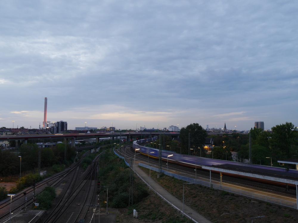 """Eine Landschaftsaufnahme von der Brücke über dem Hauptbahnhof von Ludwigshafen, man sieht einen Teil der Hochstraße, im Hintergrund Industrie und Stadtgebäude und Gleise. Durch die lange Belichtungszeit sieht man einen Zug als """"Spur""""."""