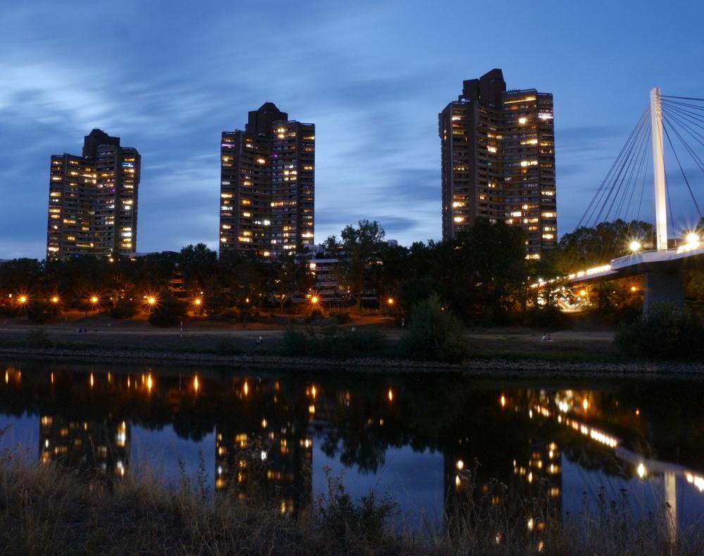 Das Foto zeigt die drei Hochhaustürme der Neckaruferbebauung Nord in Mannheim am Abend, rechts kann man einen Teil der Fußgängerbrücke Neckarsteg sehen. Die Lichter der Hochhäuser spiegeln sich im Neckar