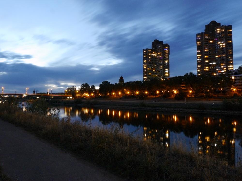 Das Foto zeigt den Neckar in Mannheim, zwei Hochhäuser der Neckaruferbebauung Nord und weiter hinten die Kurpfalzbrücke