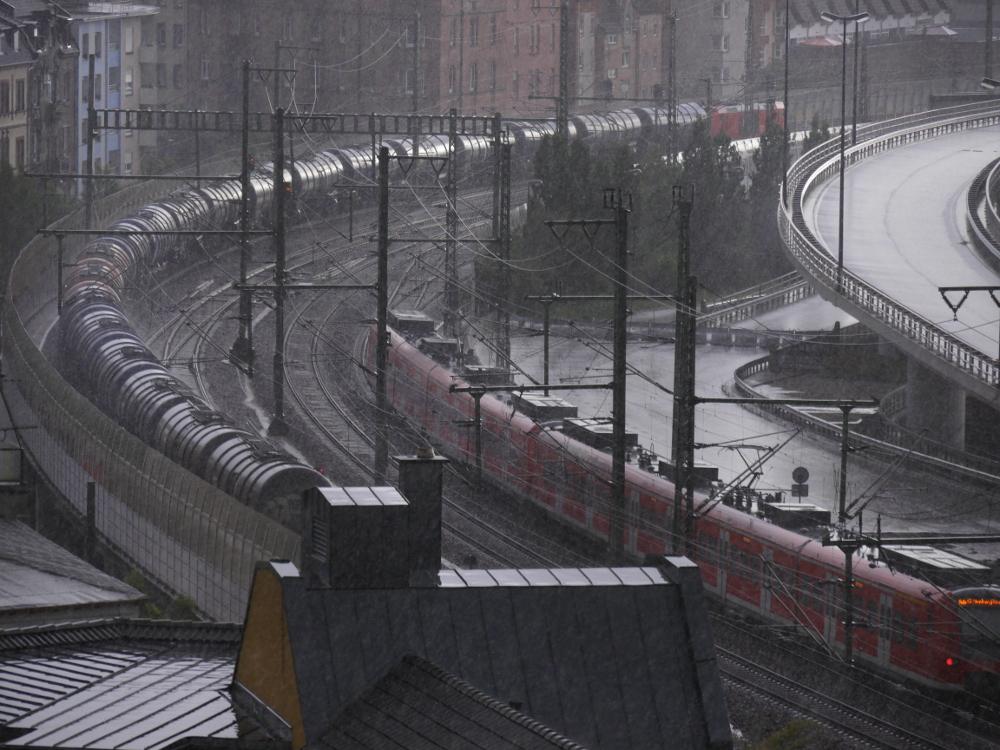Das Foto zeigt eine mehrgleisige Rechts-Kurve der Eisenbahn in der Stadt, daneben ist eine Straßenkurve. Auf dem rechten Gleis fährt eine rote Regionalbahn, auf dem linken Gleis ein Güterzug mit Kesselwagen. Und man erkennt starken Regen