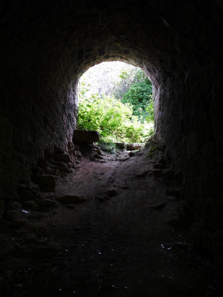 Ein kurzer Tunnel in der alten Burgruine. Man sieht das historische Gemäuer, aber auch moderne Glasscherben am Boden