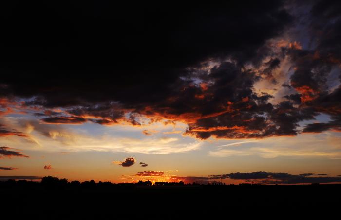 Das Foto zeigt einen dramatischen Sonnenuntergang, die Sonne ist gerade hinter dem Horizont verschwunden, es sind viele dunkle Wolken am Himmel und zwischen Horizont und den dunklen Wolken ist ein heller Streifen.