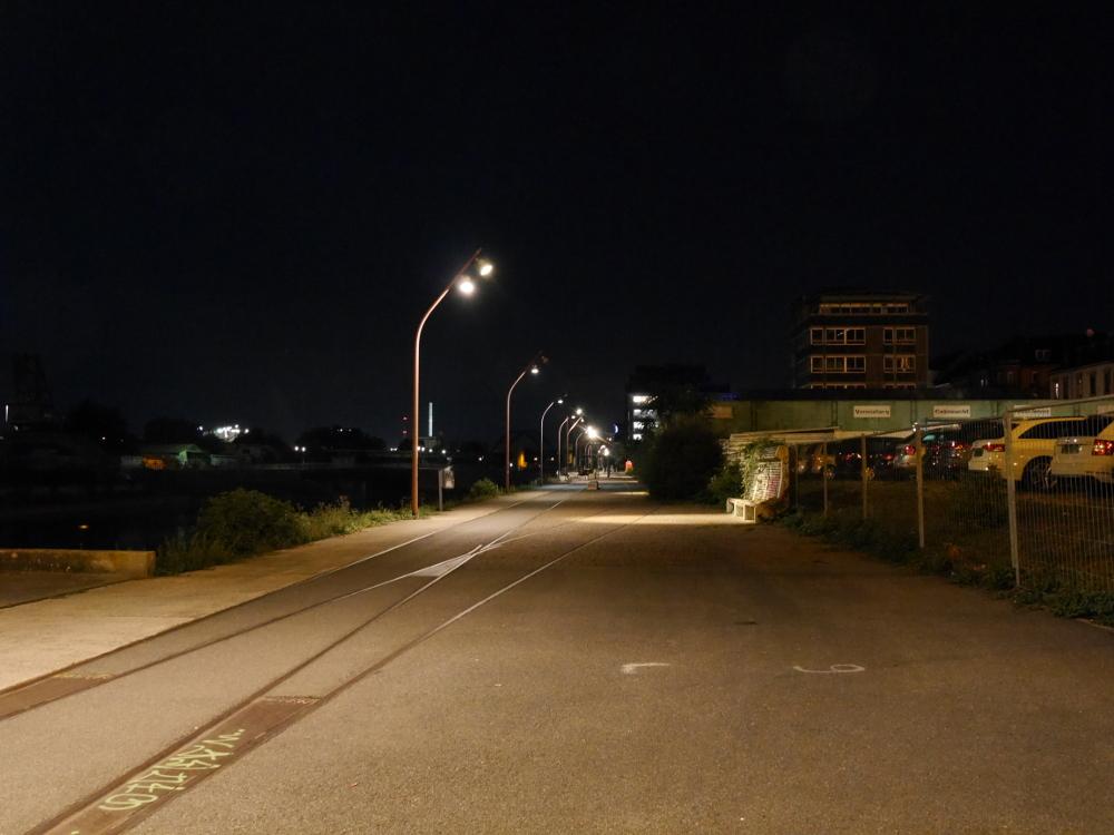 Die Nachtaufnahme zeigt einen Fußweg, der früher zu einem Industriegebiet gehörte (Schienen sind noch sichtbar) an einem Kanal, links ist der Kanal, rechts stehen Gebäude.
