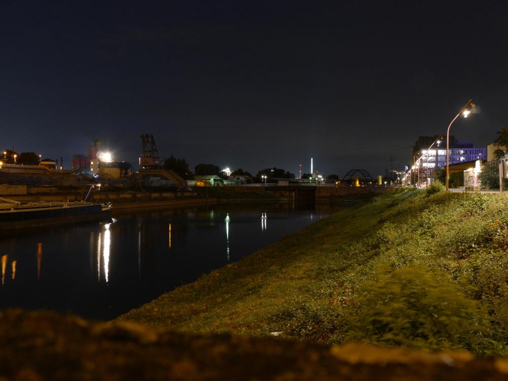 Die Nachtaufnahme zeigt den Verbindungskanal in Mannheim/Jungbusch. Auf der rechten Seite sieht man Gebäude, links am Kanal steht ein Hafenkran.