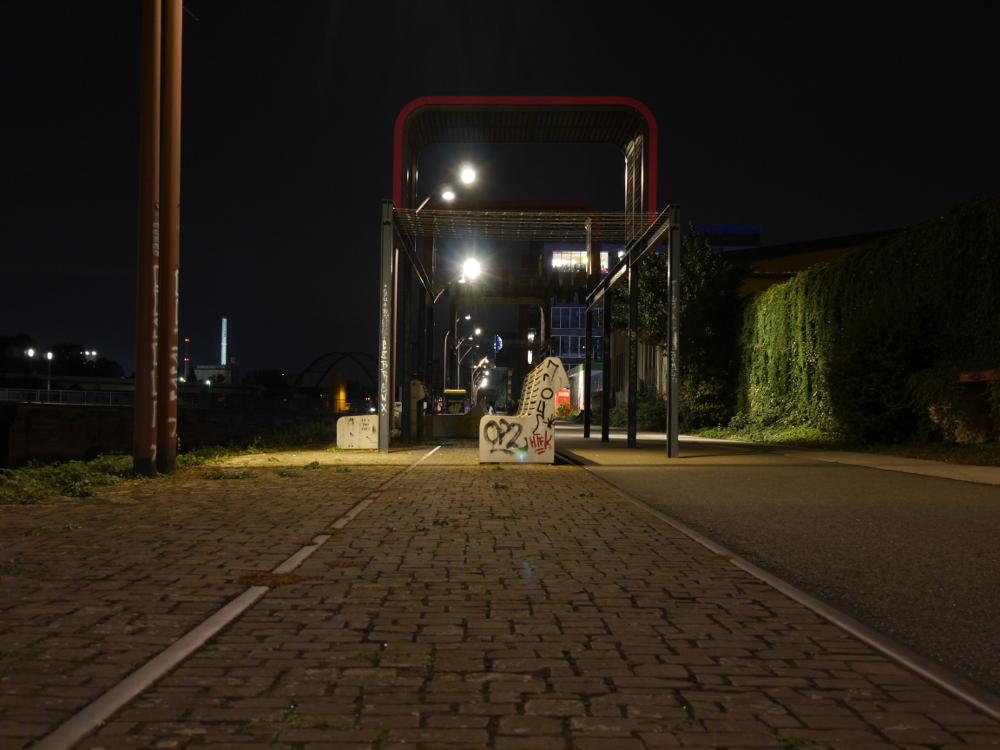Die Nachtaufnahme zeigt Bänke und andere Stadtmöbel am Fußweg am Verbindungskanal in Mannheim