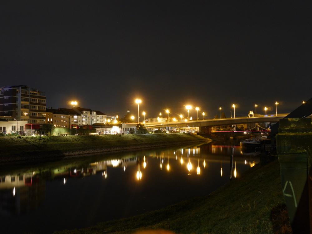 Mehrere Brücken dicht beeinander über einen Kanal, rechts im Kanal liegt ein Binnenschiff, links stehen Gebäude.