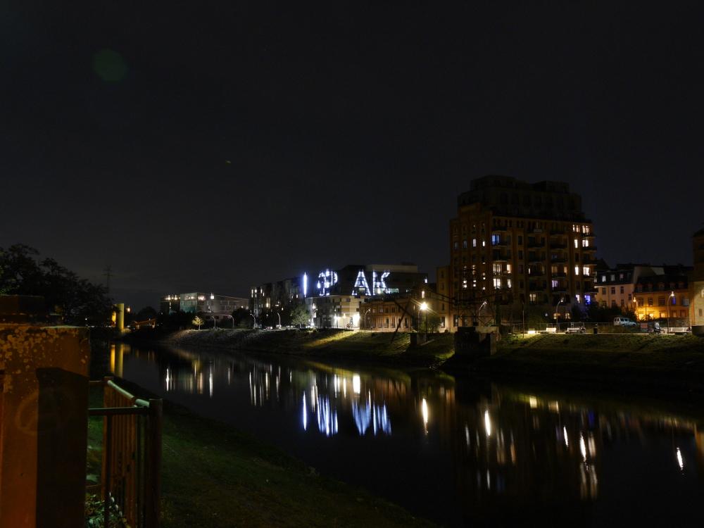 DIe Nachtaufnahme zeigt den Verbindungskanal in Mannheim/Jungbusch, auf der rechten Seite des Kanals sieht man Geäbude, darunter die Pop-Akademie mit beleuchteten Buchstaben.