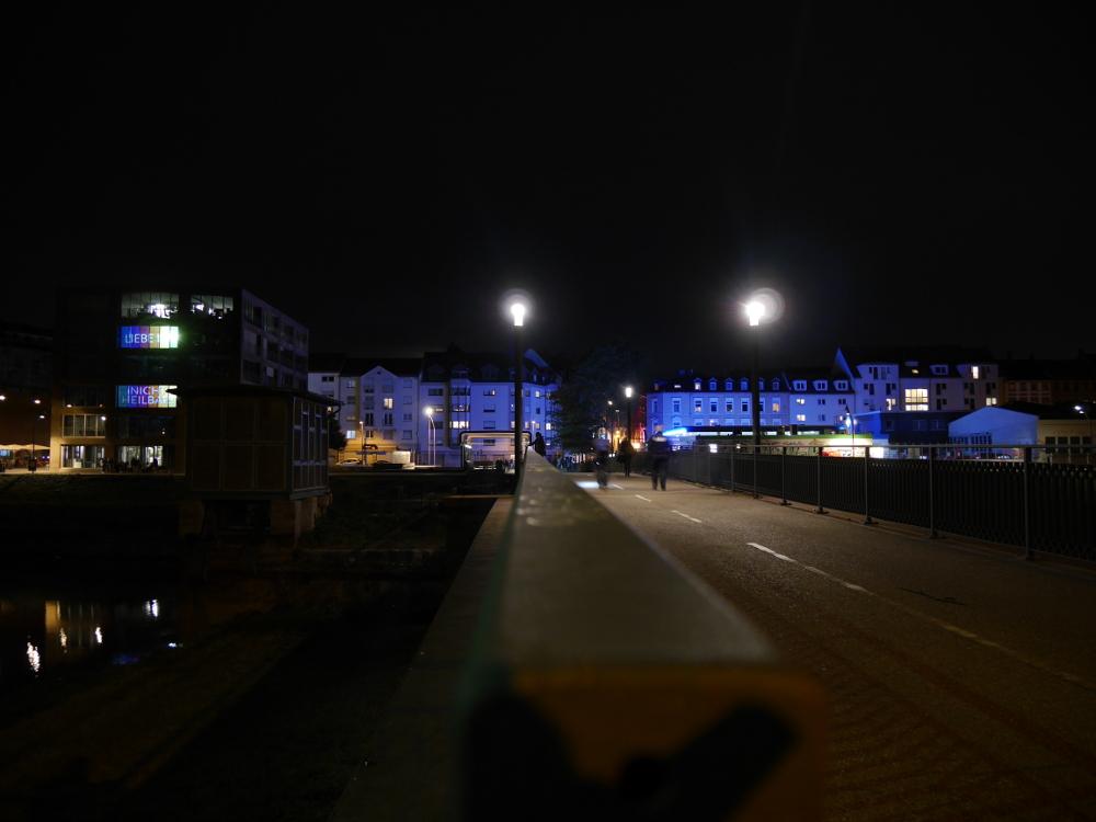 Die Nachtanfahme zeigt die Teufelsbrücke am Verbindungskanal. Die Kamera steht in höhe des Handlaufs der Brücke,, man sieht Gebäude dieren Fassade von einer Tankstelle blau beleuchtete werden.
