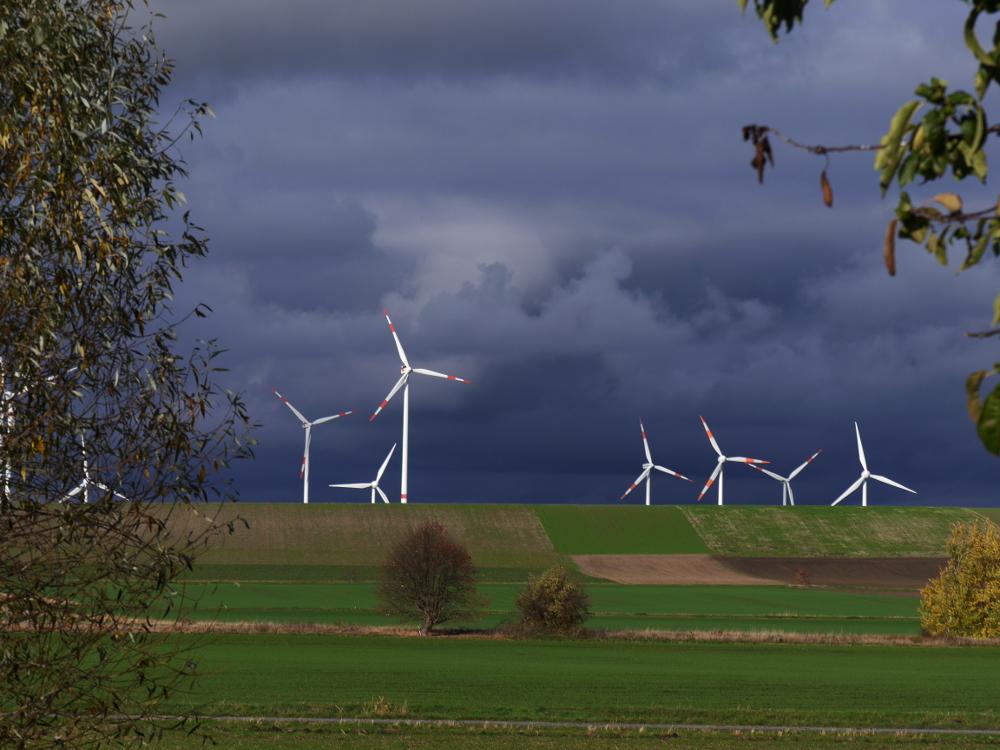 Eine Landschaftsaufnahme, rechts und Links sind Teile von Bäumen, man sieht einen Anstieg/Hügel und dahinter stehen Windräder. Der Himmel ist von dramtisch dunklen Wolken geprägt.