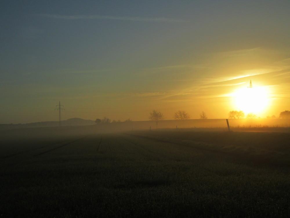 Eine Landschaftsaufnahme mit Gegenlicht bei leichten Nebel, man sieht links die aufgehende Sonne, eine Straße und weiter hinten leichten Nebel, durch das Bild geht eine Freileitung und im Hintergrund ist der Heseberg. Das Bild ist nicht ganz gerade.
