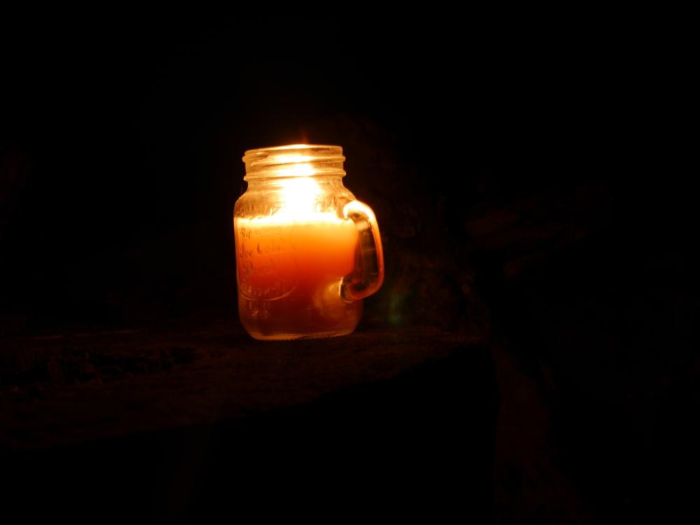 Foto von einer Kerze in einem Glas, die brennt und bei Dunkelheit auf einem Holzblock steht. Kann gut als Symbolfoto verwendet werden.
