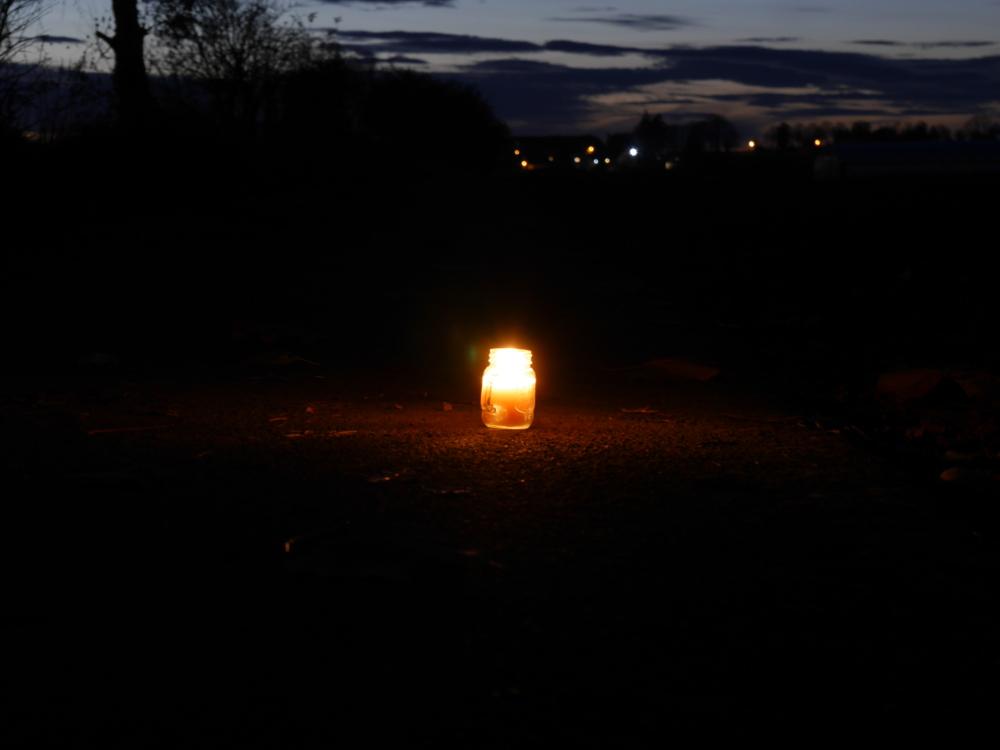 Eine Aufnahme am späten Abend, ene Kerze im Glaus auf einem Feldweg, im Hintergrund sieht man noch ein wenig Resthelligkeit vom Tag und unscharf die Lichter vom nächsten Ort