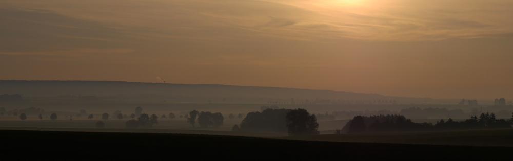 Eine Landschaftsaufnahme beim Sonnenuntergang, über den Bäumen und Hügeln liegt leichter Nebel.