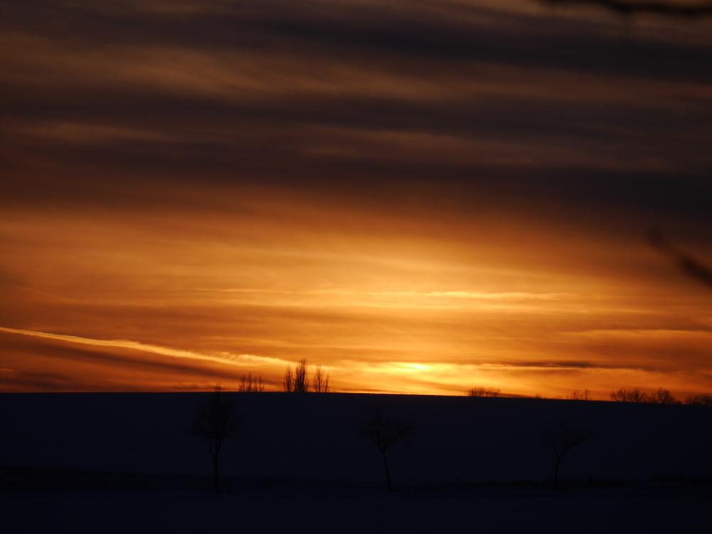 Ds Foto zeigt einen dramtischen Sonnenuntergang im Winter. Über der Schneebedeckten Landschaft ist der Himmel bzw. die Wolken durch das letzte Sonnenlicht orange erleuchtet.