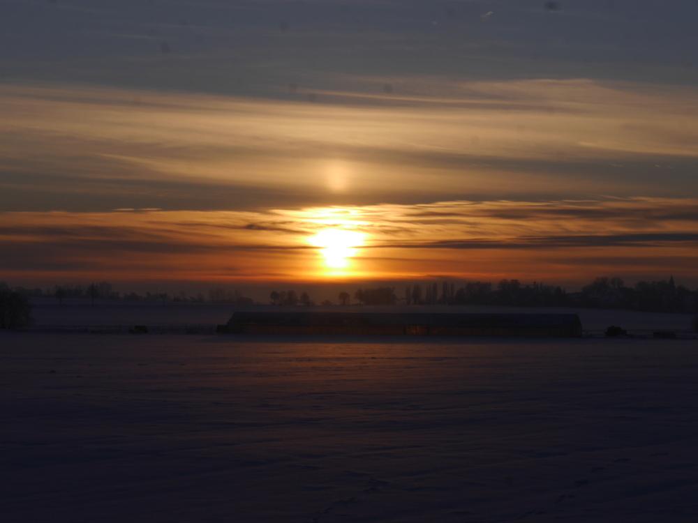 Das Foto zeigt einen dramatischen Sonnenuntergang im Winter, die Landschaft ist weiß und Schneebedeckt, darüber geht die Sonne unter.