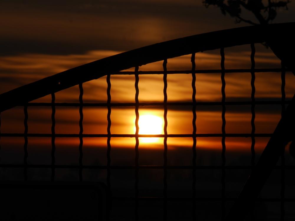Das Foto zeigt einen dramatischen Sonnenuntergang der durch das GItter eines Tors aufgenommen wurde, die Gitterstäbe sind schwarz und scharf während die Sonne und die durch die Sonne orange eingefärbten Wolken in Unschärfe verschwinden.