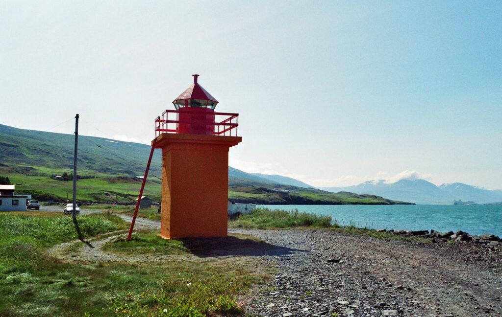 Ds Foto zeigt einen Leuchtturm an einer Küste in Island. Der Leuchtturm ist etwa ein Stockwerk hoch und leuchtend orange/rot gestrichen. Im Hintergrund sieht man das Meer und die grüne isländische Landschaft.