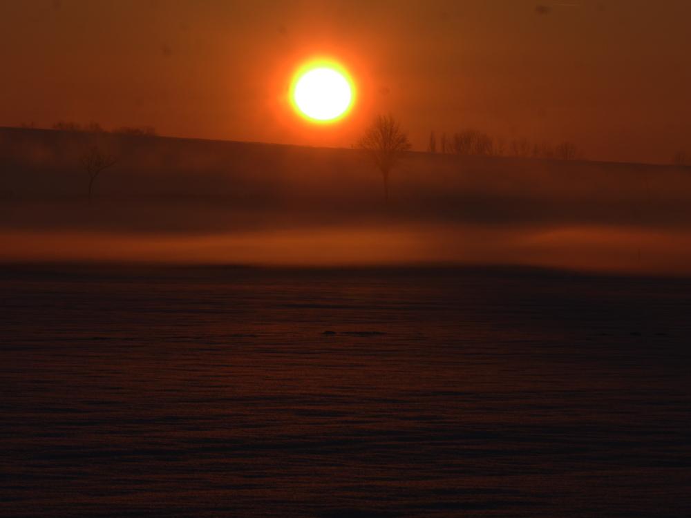 """Ein experimentelles-Sonneuntergangsfoto. Die Landschaft is Schneebedeckt, die Sonne hat alles in orangenes Licht gefärbt und es gibt leichten Dunst, der das LIcht """"weich"""" macht."""