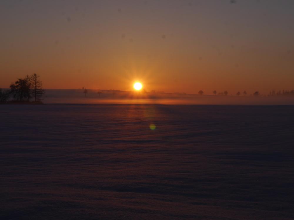 Ein Sonnenuntergang bei Schnee. Die Sonne ist kurz vor dem Horizont, die Landschaft vom Schnee weiß und es liegt ein leichter Dunst über dem Boden,