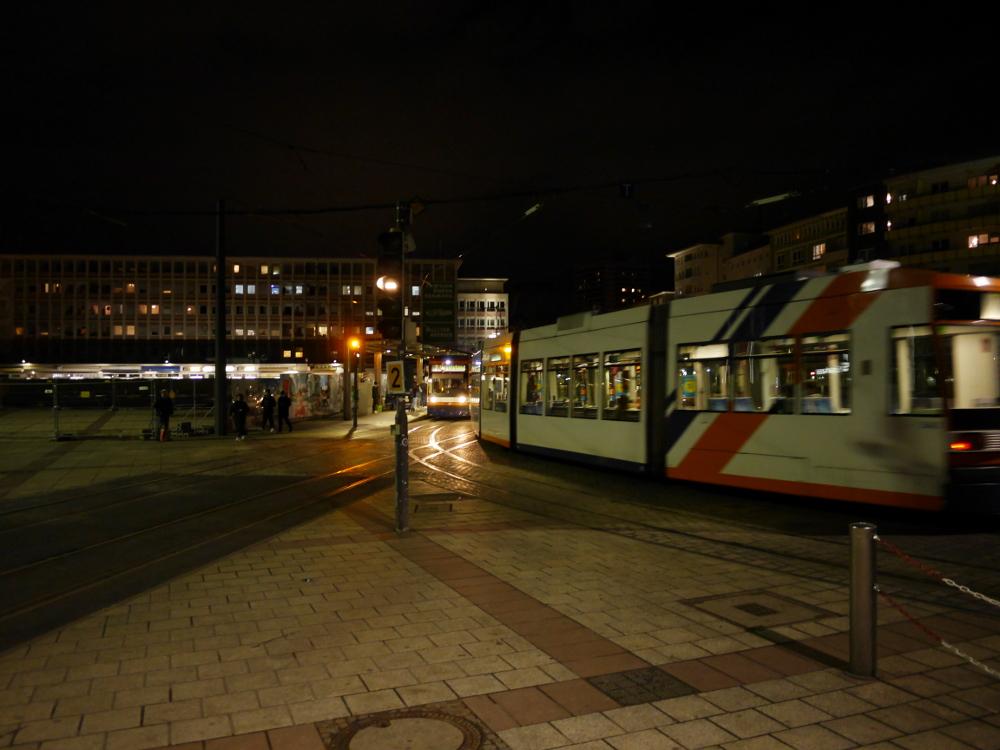 Eine nächstliche Straßenszene auf einem Platz mit Straßenbahnen, von eine Strecke rechts kommt eine Straßenbahn und fährt Richtung Haltestelle. An der Haltestelle steht schon eine Straßenbahn, die in Gegenrichtung fährt, und wartet.