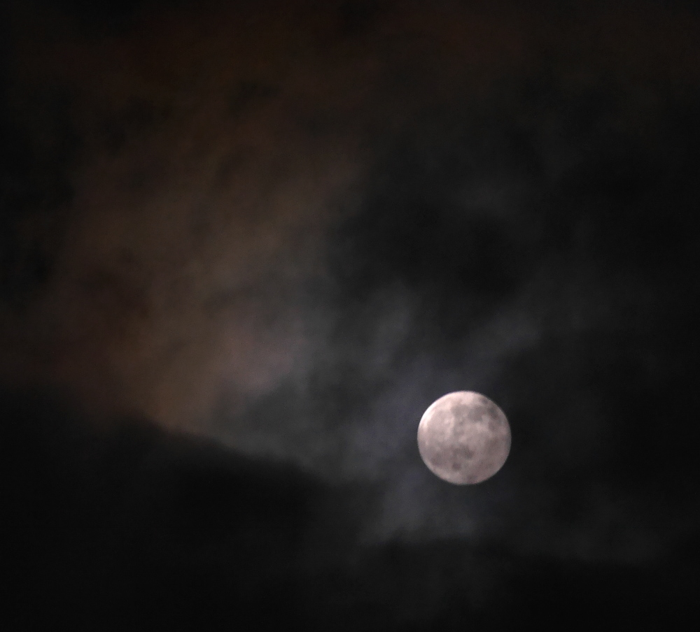 Das Foto zeigt im unten, rechten drittel den Vollmond hinter einer leichten Wolkenschicht. Insbesondere Links oben sieht mand ie Wolken im Mondlicht schimmern.