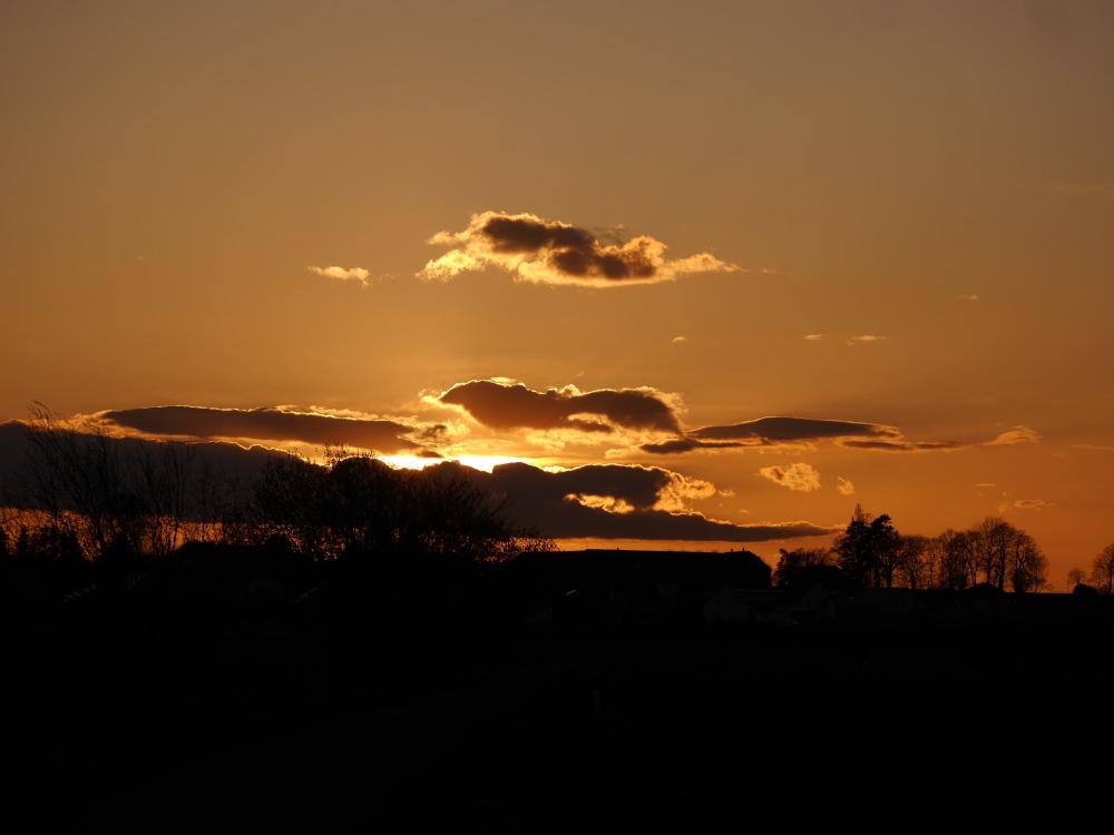 Ds Foto zeigt einen dramatischen Sonnenungergang, die Sonne ist teilweise von Wolken bedeckt und der Himmel glüht in warmen Orange-Tönen.