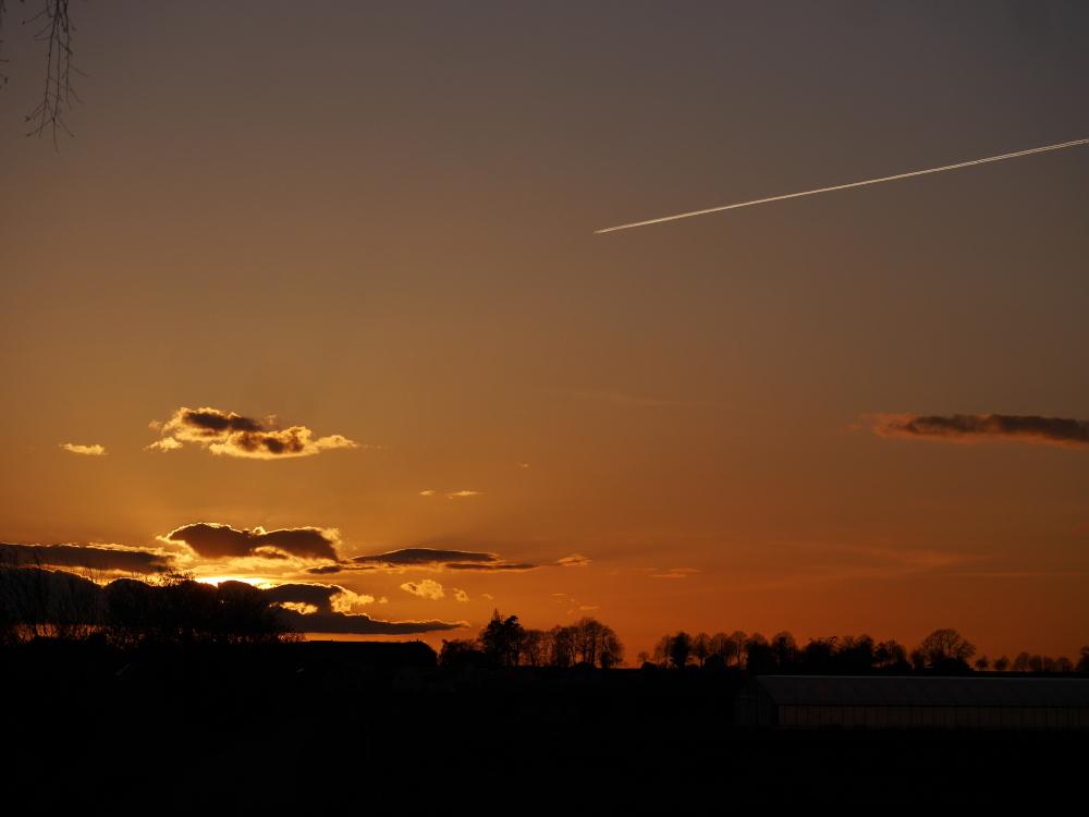 Ds Foto zeigt einen dramatischen Sonnenungergang, die Sonne ist teilweise von Wolken bedeckt und der Himmel glüht in warmen Orange-Tönen. Die Sonne steht schon tief und man sieht oberhalb der Sonne von rechts kommend den Kondensstreifen eines Flugzeugs.