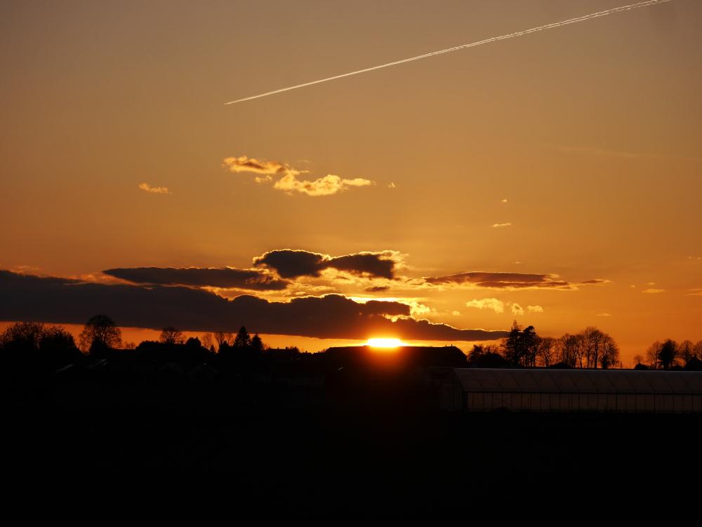Ds Foto zeigt einen dramatischen Sonnenungergang, die Sonne ist teilweise von Wolken bedeckt und der Himmel glüht in warmen Orange-Tönen. Die Sonne leichtet zwischen den Wolken und einem Hausdach wie dorch einen Spalt. Sie steht schon tief und man sieht oberhalb der Sonne von rechts kommend den Kondensstreifen eines Flugzeugs.