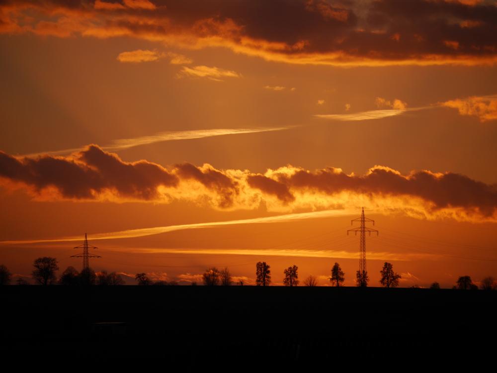 Eine Landschaftsaufnahme kurz nach dem Sonnenuntergang, die Sonne ist schon verschwunden, sie beleuchtet aber noch die Landschaft und die Wolken in dramatischem Orange. In der Landschaft sieht man zwei Masten einer Freileitung.