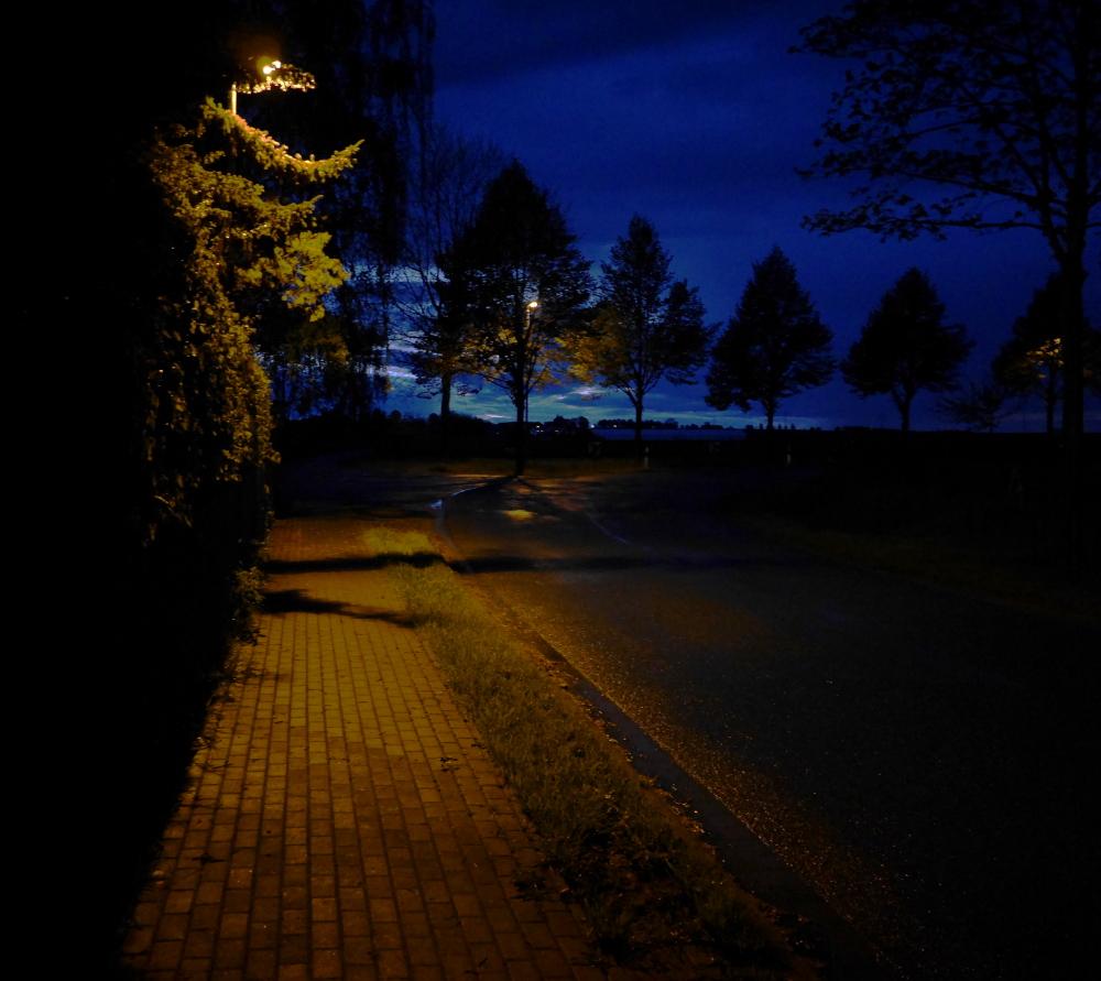 Die Nachtaufnahme einer Kurve nach rechts an einem Ortsausgang. Es hat kürzlich geregnet, man sieht Wasser auf der Straße und das Licht von Staraßenlaternen, die Laternen selbst sind allerdings häufig von Büschen und Bäumen verdeckt. Im Hintergrund sieht man in den blauen Wolken einige hellblaue Lücen und ein weiteres Dorf.
