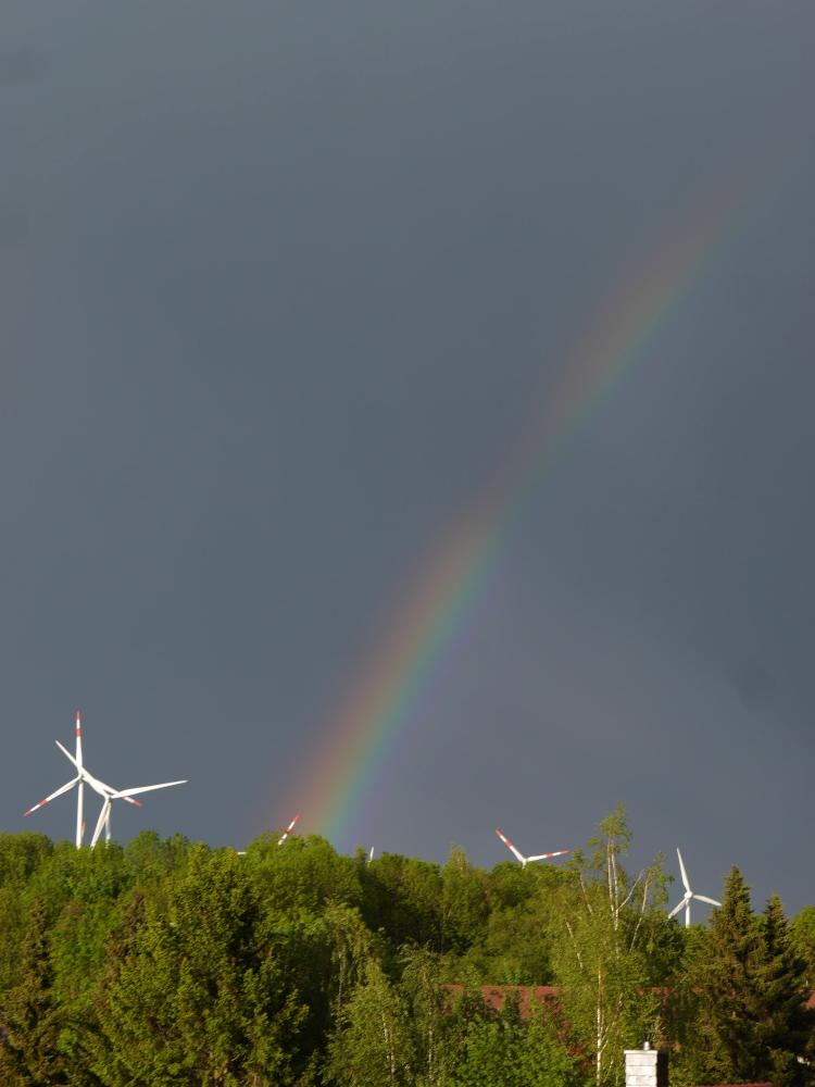 Eine Landschaftsaufnahme mit Regenbogen am dunklen Himmel. Trotz des dunklen Himmels scheint die Sonne und bestraht die im unteren Bildbereich sichtbaren Bäume, die in sehr sattem Grün stehen, sowie die Rotoren von mehreren Windkraftanlagen und zwischen den Bäumen kann man auch Dächer von Häusern erkennen.